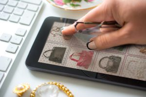 older woman with manicured hand and reading glasses ready to use tapping an her tablet. Buying a vintage handbag online with a mini tablet. The website is fictional